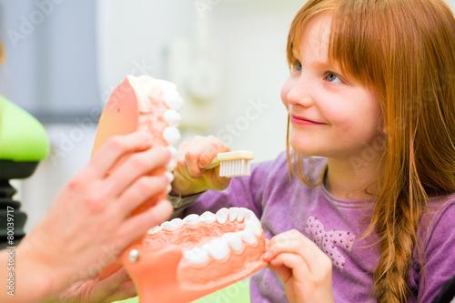 Leinwandbild Motiv Zahnärztin erklärt Mädchen Zähneputzen