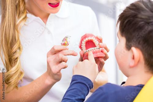 Zahnärztin erklärt Junge Zahnspange  - 80039779