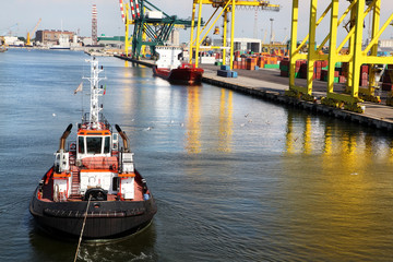 Tugboat pulling container ship