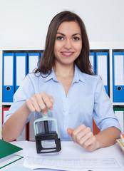 Frau mit langen braunen Haaren und Stempel im Büro