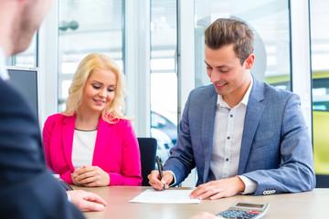 Paar verhandelt Kaufvertrag für Neuwagen