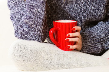 Closeup female hand holding red mug hot drink