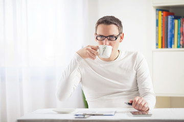 Young businessman having a cup of coffee while working at home