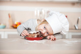 Fototapety Little funny girl with chef hat eating cake