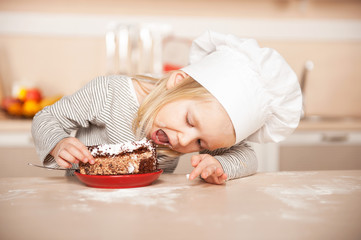 Little cute girl with chef hat eating cake