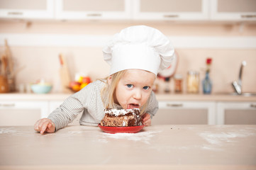 Funny girl with chef hat eating cake