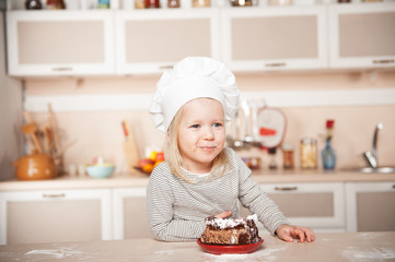 Funny girl with chef hat and mouth full of cake