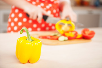 Close up photo of woman chopping paprika for salad