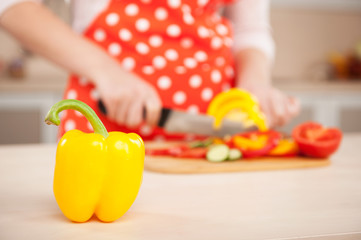 Close up photo of woman chopping yellow paprika
