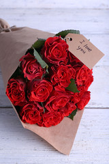 Bouquet of red roses with tag wrapped in paper