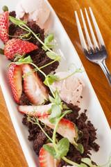 dessert of crumbled chocolate cake, gelato and strawberries