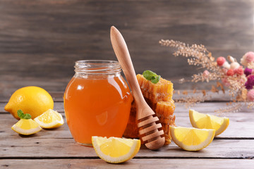 Delicious honey with lemon on table on wooden background