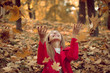girl throws autumn leaves