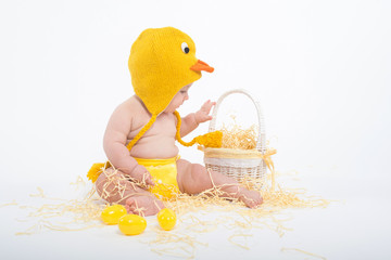 Baby in a costume of chicken looking in white wicker basket
