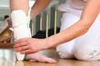 Leinwanddruck Bild - Ärztin oder Therapeutin beim Anlegen einer Knöchelbandage