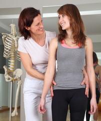 Physiotherapeutin mit Händen an Hüfte einer Patientin