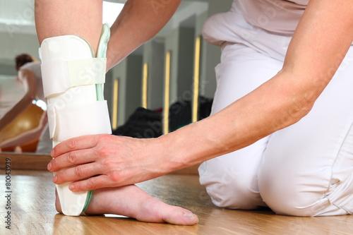 Leinwanddruck Bild Ärztin oder Therapeutin beim Anlegen einer Knöchelbandage