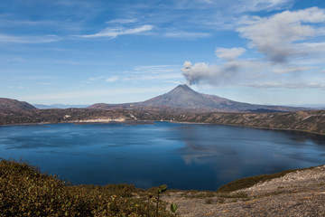 Volcanic eruption. Smoke over mountain lake.