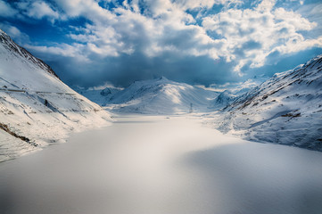 Alps in winter with snow and frozen lake