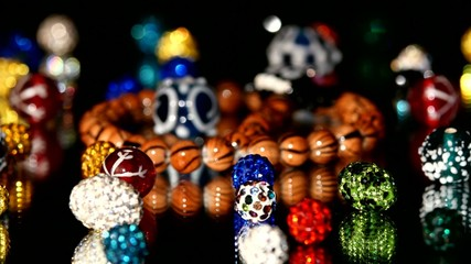 Lot of varicolored beads on black background, rotation