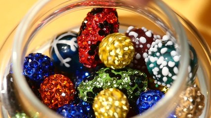 Varicoloured beads falls into the jar on yellow background
