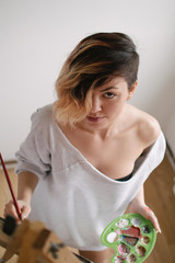 A girl with short hair smiling while painting