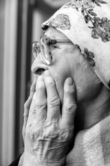 elderly woman near window at home.