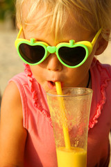 little girl drinks fruit cocktail through a straw