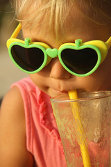 little girl drinking fruit cocktail through a straw