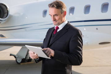 executive business man in front of corporate jet looking at tabl