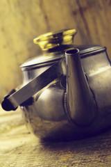 metal tea kettle on wooden background
