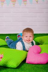 Little baby sleeping on a green cushion