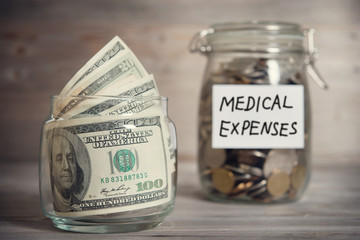 Dollars and coins in jar with medical expenses label