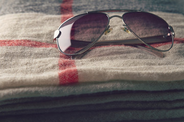 Pair of cool sunglasses on folded beige scarf accessory