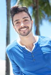 Modischer junger Mann mit Palmen lacht fröhlich