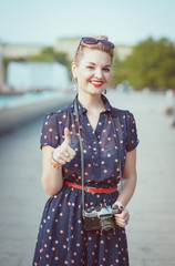 Beautiful woman in vintage clothing with retro camera showing th