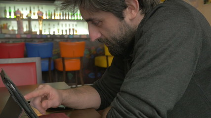 Businessman using a tablet pc in a bar