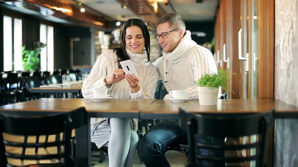 Couple doing selfie on smartphone in the cafe