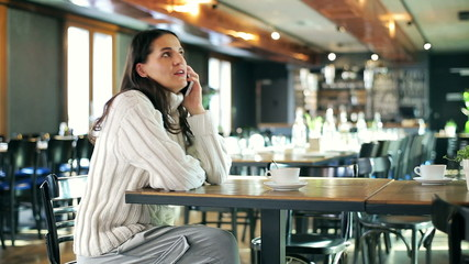 Happy woman chatting on cellphone in the cafe
