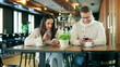 Couple sitting in silence in the restaurant and using cellphones