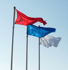 White, blue and red flags against sky.