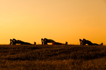 Girls practicing yoga in sunset