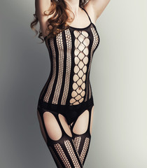Woman in black fishnet body stocking suit