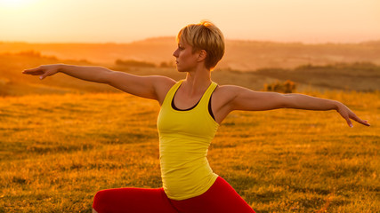 Woman practicing yoga in sunset