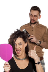 hairdresser doing his happy client hair with a  comb