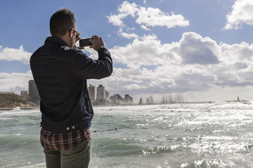 Man taking picture on his phone by the sea