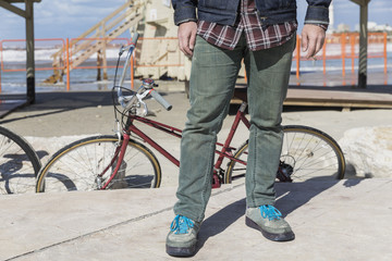 Closeup of man's legs standing inform of a vintage bicycle