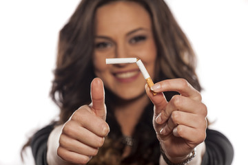 happy young woman hold a broken cigarette and showing thumb up