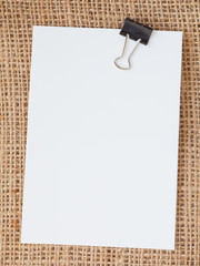 Blank paper note and metal clip on brown fabric background..