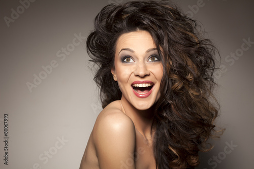 happy beautiful brunette posing in the studio - hair styling